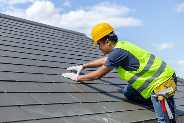 worker with white gloves replacing gray tiles or shingles on a house