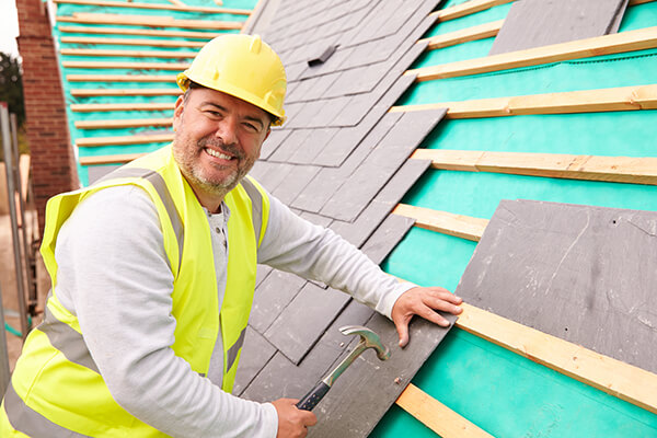 A roof contractor installing a new roof shingles