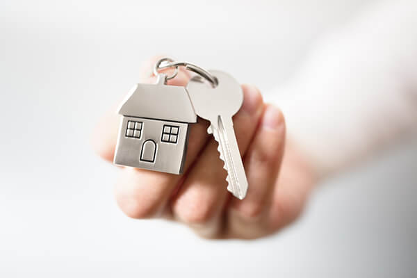 A keychain with a metal house and a key
