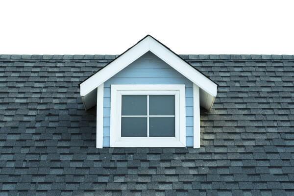 A dormer window on top of an asphalt shingle roofing