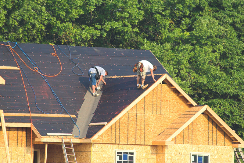 Team of roof contractors working on the roof