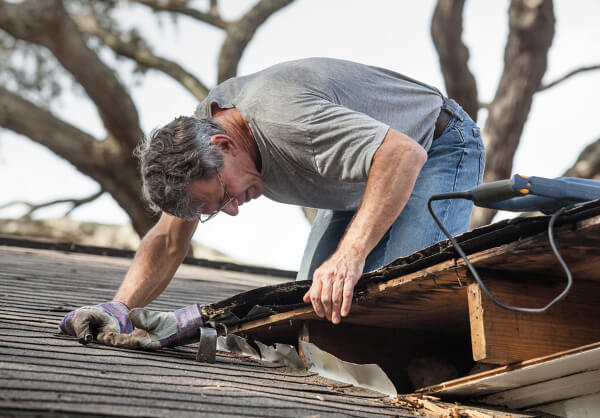 man on top of roof removing old material